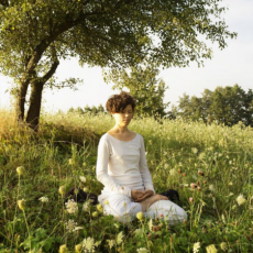 woman meditating in field
